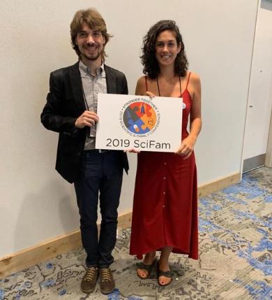 """El Marc i la Laura agafen un cartell que diu """"2019 SciFam""""."""